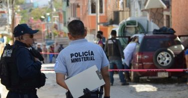 Police officers guard a crime scene where mutilated bodies were found on the roof of a vehicle, in Chilpancingo